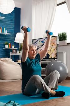 Mulher sênior aposentada sentada no tapete de ioga em posição de lótus, levantando as mãos alongando o músculo do braço, fazendo exercícios de fitness usando halteres durante o treino de bem-estar. atleta aposentado emagrecimento peso