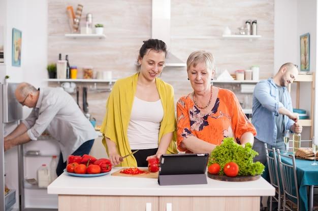 Mulher sênior, assistindo a receita de salada na mesa, enquanto cozinhava junto com sua filha na cozinha. filha mãe preparando o almoço.