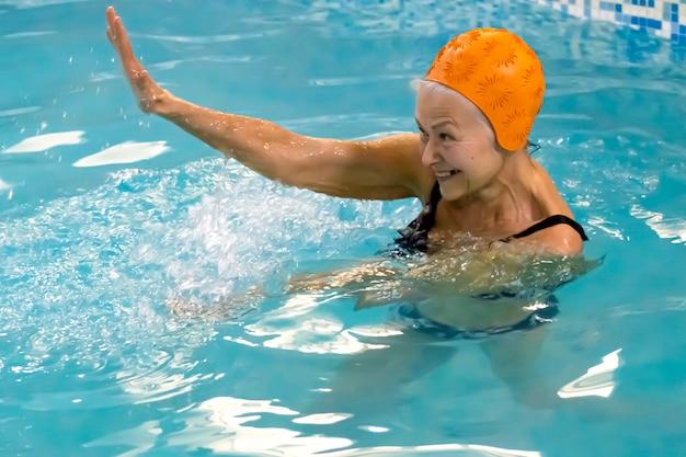 Mulher sênior ativa e feliz tendo aulas de ginástica aquática na piscina