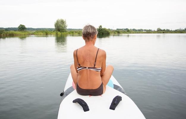 Mulher sênior ativa em maiô sentado no surf na água. vista traseira. paddle boarding.
