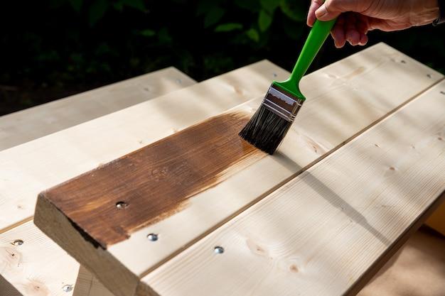 Mulher sênior ativa, pintando algumas peças de madeira, madeira por cor de tinta marrom com pincel. trabalhador pintando uma prancha de madeira