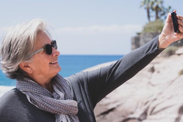 Mulher sênior atraente em férias no mar usando telefone para selfie e sorrindo feliz aposentada relaxa