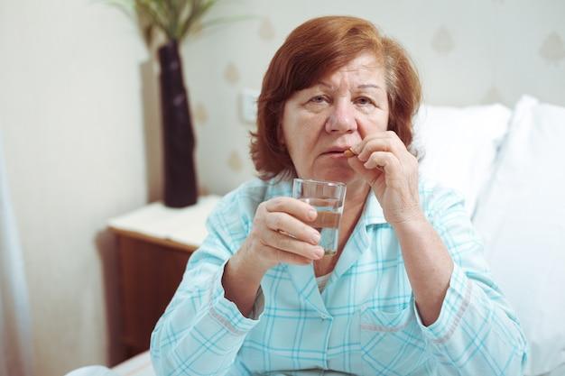 Mulher sênior beber remédio na cama, pessoa idosa solitária pegou uma gripe.