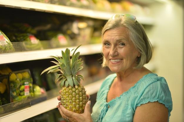 Mulher sênior bonita feliz em um mercado