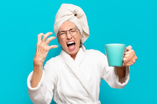 Mulher sênior bonita vestindo roupão de banho e tomando um café
