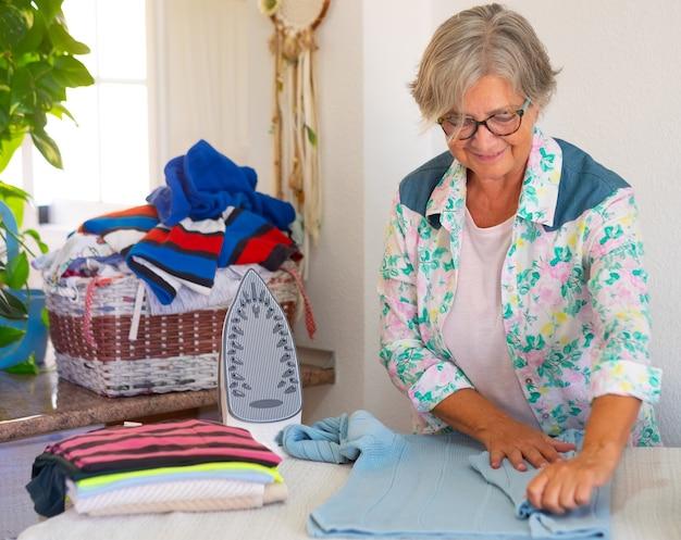 Mulher sênior caucasiana em casa passando roupa em um canto