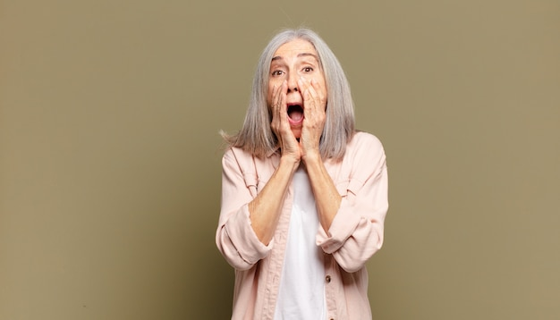 Mulher sênior chocada e assustada, parecendo apavorada com a boca aberta e as mãos nas bochechas