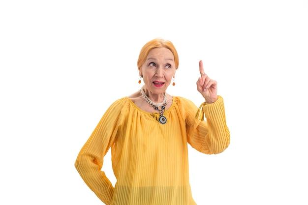 Mulher sênior com dedo levantado, senhora pensativa sobre filosofia e moral de fundo branco
