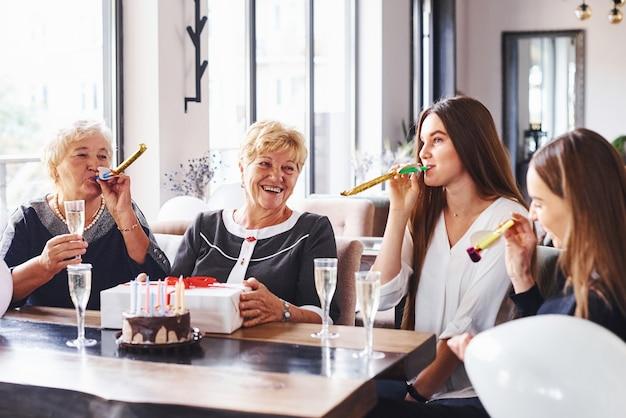 Mulher sênior com família e amigos comemorando um aniversário dentro de casa.