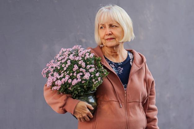 Mulher sênior com flores em vasos. mulher idosa em um moletom da moda carregando um vaso com flores frescas