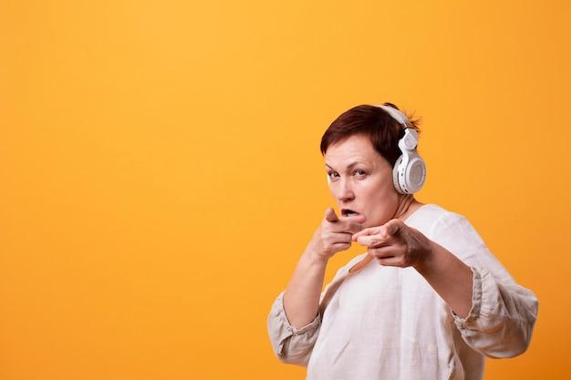 Mulher sênior com fones de ouvido apontando