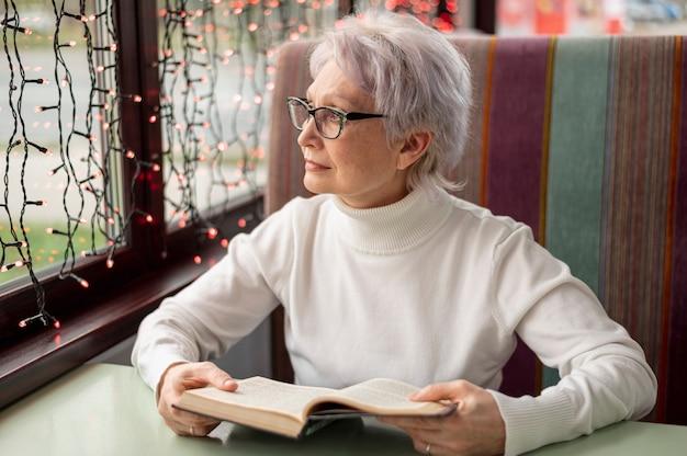 Mulher sênior com livro olhando na janela