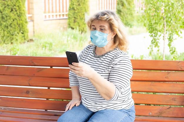 Mulher sênior com máscara facial médica usando o telefone para procurar notícias. conceito de quarentena de coronavírus. poluição do ar