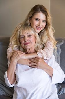Mulher sênior com neta ou filha abraçando no sofá