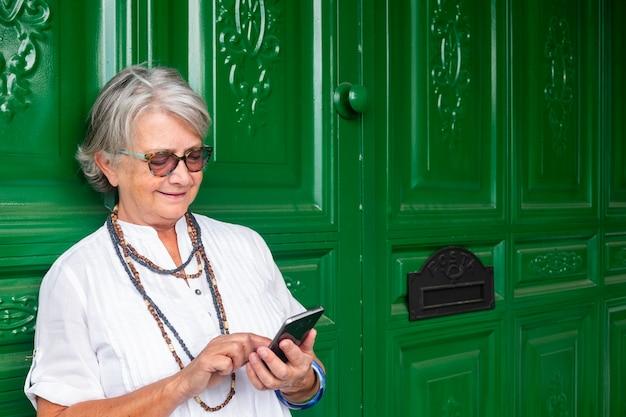 Mulher sênior com óculos e cabelos grisalhos em pé e usando o telefone celular. atrás dela, uma grande porta de madeira verde com a caixa de correio.