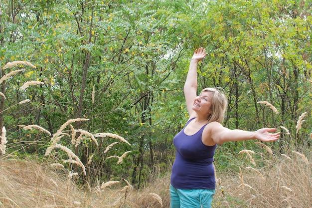 Mulher sênior com os braços para cima e respirando profundamente ao ar livre com a natureza no fundo do parque.