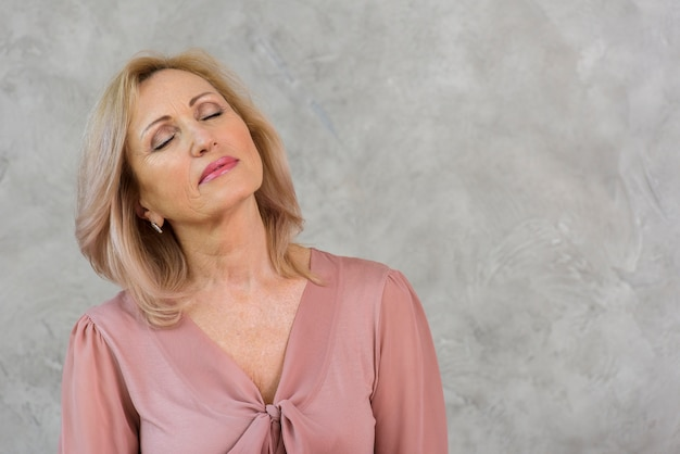Mulher sênior com os olhos fechados