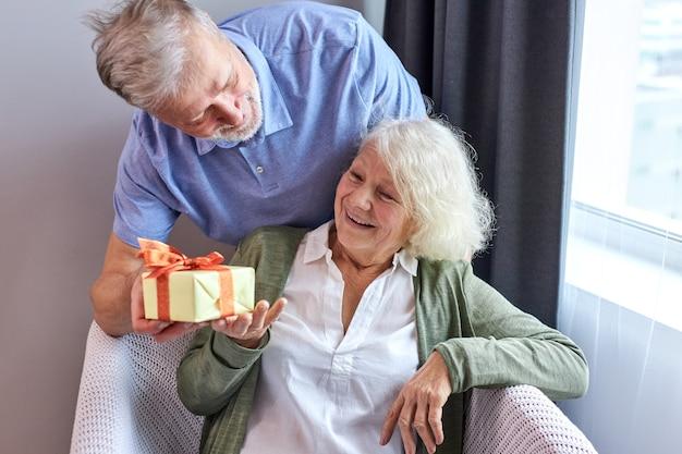 Mulher sênior com rosto satisfeito recebendo uma caixa de presentes com seu belo marido, um casal de idosos grisalhos comemorando o aniversário de uma mulher, um homem a parabeniza