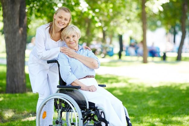 Mulher sênior com seu cuidador ao ar livre