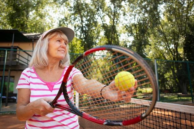 Mulher sênior com tiro médio jogando tênis na natureza