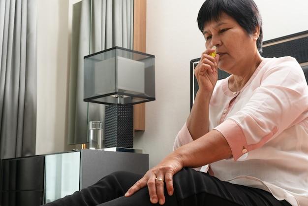 Mulher sênior com tontura de headhache e sais de cheiro