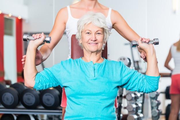Mulher sênior, com, treinador, em, ginásio, levantamento, dumbbell