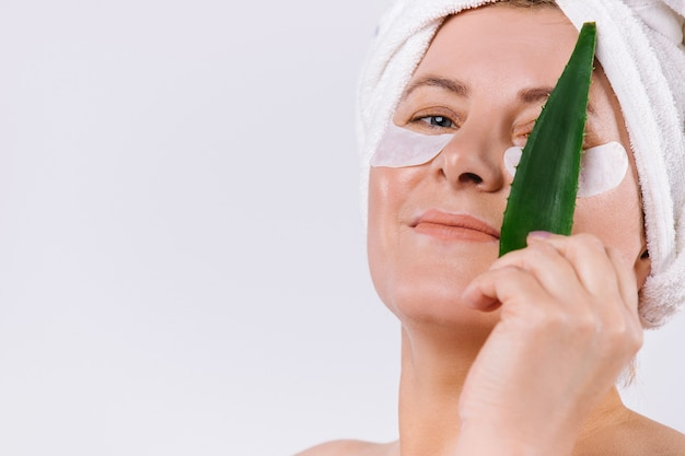 Mulher sênior com uma toalha na cabeça cobrindo os olhos com uma folha de aloe vera em um fundo branco com espaço lateral vazio. foto de alta qualidade