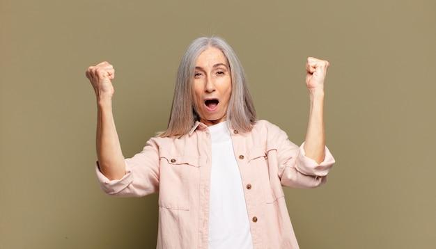 Mulher sênior comemorando um sucesso inacreditável como uma vencedora, parecendo animada e feliz por dizer