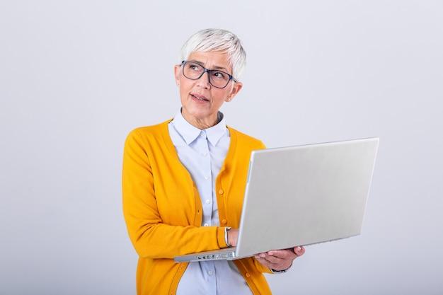 Mulher sênior confusa que usa o computador portátil.