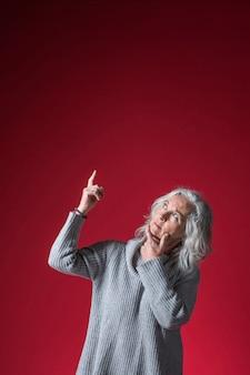 Mulher sênior contemplada, apontando o dedo para cima de pé contra um fundo vermelho