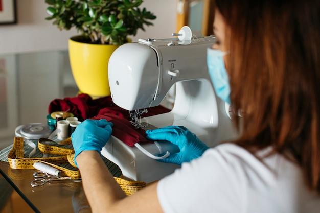 Mulher sênior costura com uma máquina de pano máscaras