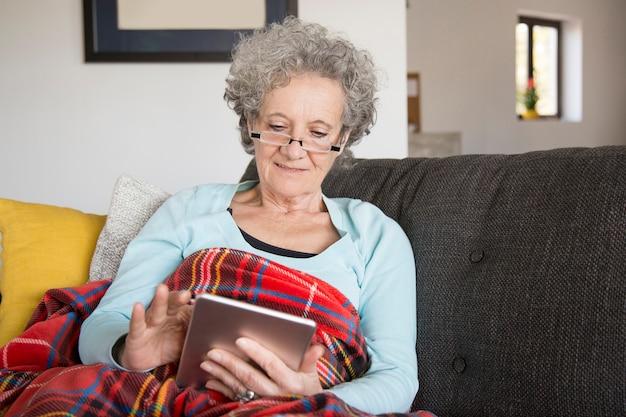 Mulher sênior curiosa sentada no sofá e usando o gadget