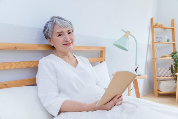Mulher sênior da ásia está sentada na cama e lendo o livro.