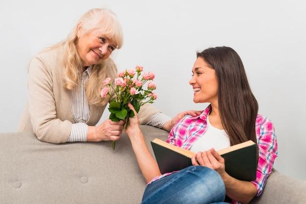 Mulher sênior, dar, rosa, buquê, para, dela, filha, segurando, livro, em, mão, sentar sofá