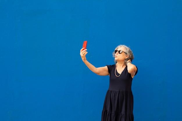 Mulher sênior de cabelos grisalhos tirando uma selfie com um smartphone vermelho contra uma parede azul