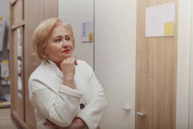 Mulher sênior de compras na loja de móveis