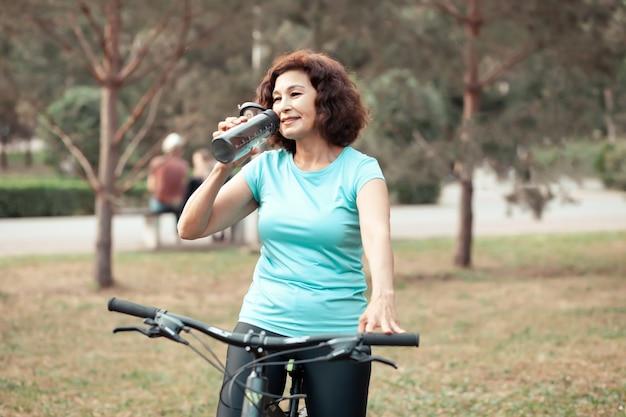 Mulher sênior de meia-idade no ciclo de bicicleta passeio no parque rural ao ar livre e beber água da garrafa.
