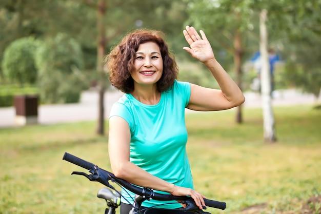 Mulher sênior de meia-idade no passeio de ciclo de bicicleta no parque rural ao ar livre.