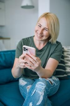 Mulher sênior de meia idade sorridente atraente usando telefone inteligente enquanto está sentado no sofá em casa