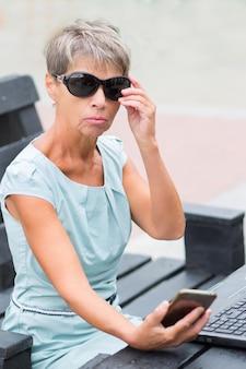 Mulher sênior de negócios da moda com telefone e notebook em vestido azul