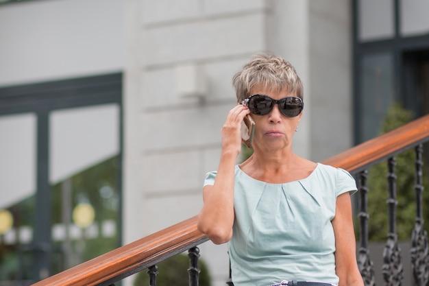 Mulher sênior de negócios da moda com telefone e vestido azul