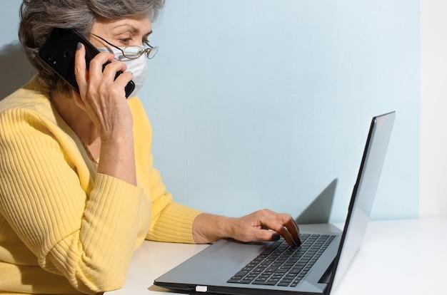 Mulher sênior de óculos e máscara médica, chamando por telefone. mulher idosa usando laptop em casa. conceito de consulta online, trabalho remoto, novo normal.