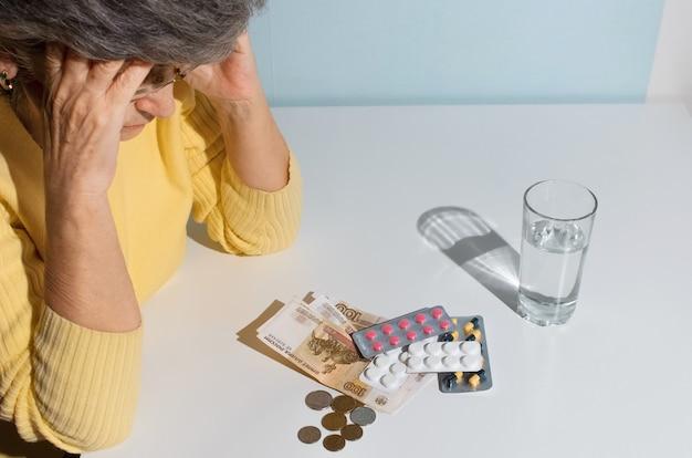 Mulher sênior de óculos, olhando para o dinheiro e os comprimidos em cima da mesa. conceito de depressão, preço do medicamento, custo do tratamento