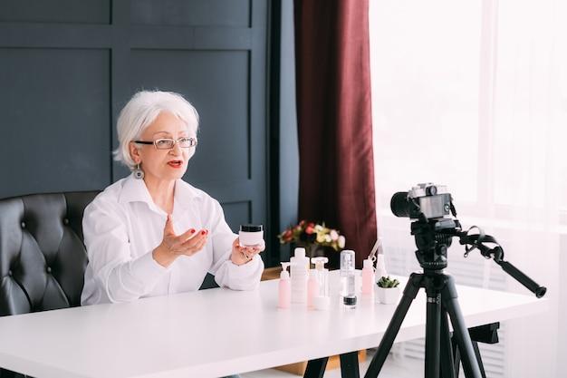Mulher sênior de sucesso. estilo de vida de blogging. senhora idosa fazendo vídeo apresentando produtos de cuidados da pele.
