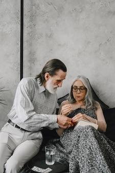 Mulher sênior deitada na cama e tomando comprimidos com marido carinhoso. doença, quarentena.