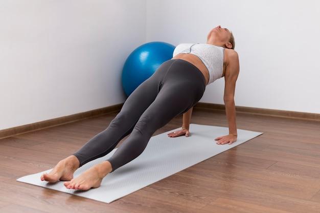 Mulher sênior dentro de casa fazendo exercícios com bola de fitness
