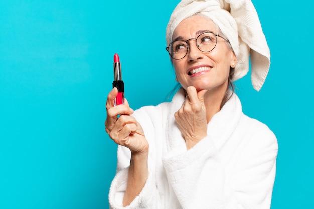 Mulher sênior depois do banho se maquiando e vestindo um roupão de banho