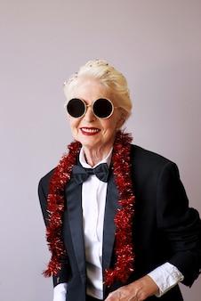 Mulher sênior descolada de smoking e óculos escuros na festa