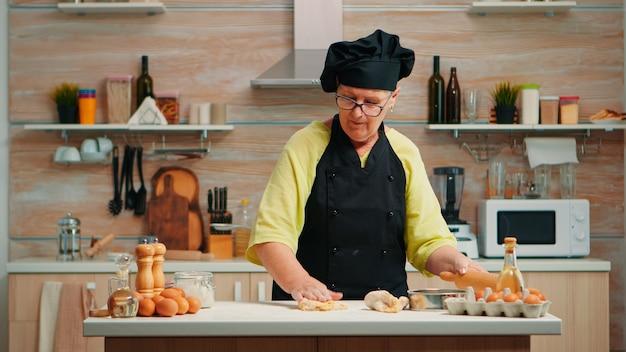 Mulher sênior desenrolando a massa para preparar pão caseiro. feliz chef idoso com bonete preparando ingredientes crus para assar pizza tradicional, polvilhando, peneirando a farinha na mesa da cozinha.