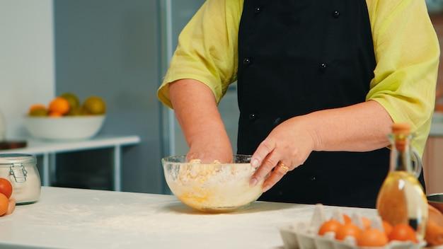 Mulher sênior do chef misturando ingredientes de pão à mão na cozinha em casa em uma tigela de vidro. padeiro idoso aposentado com bonete amassando ovos frescos rachados com farinha de trigo fazendo bolo caseiro e pão